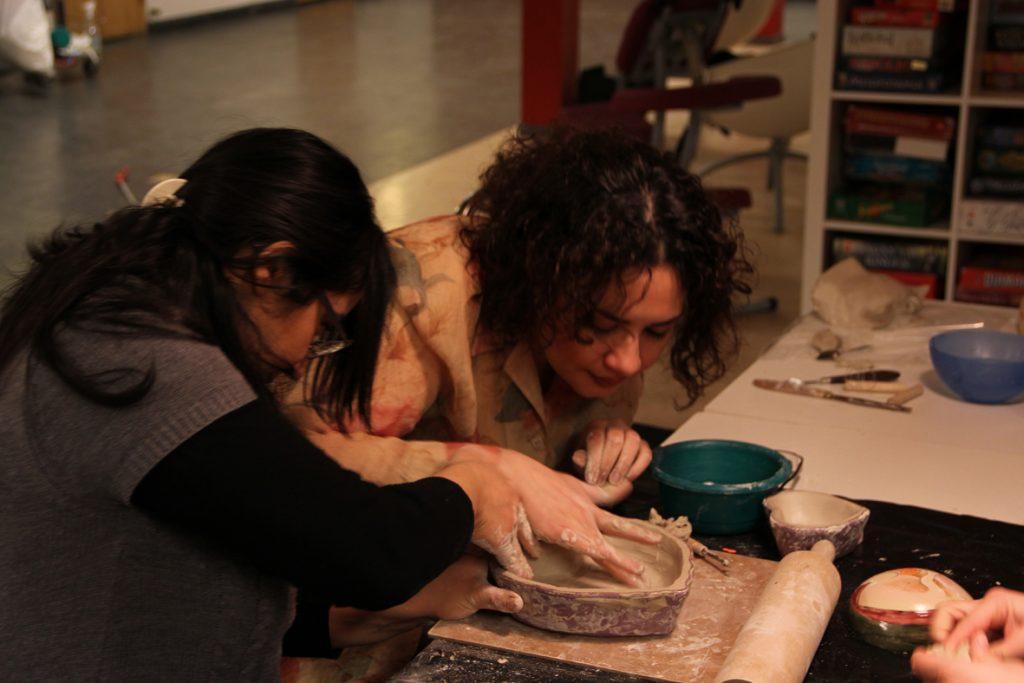 två personer som jobbar med lera